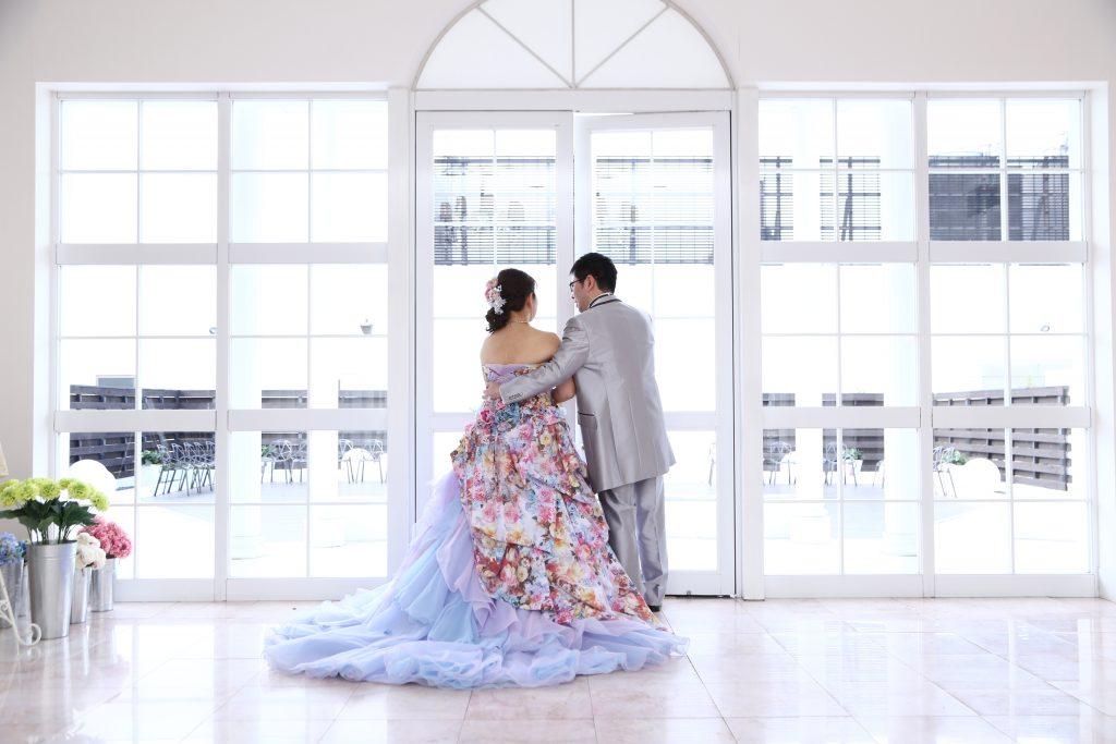 カラードレスとタキシードを着た新郎新婦