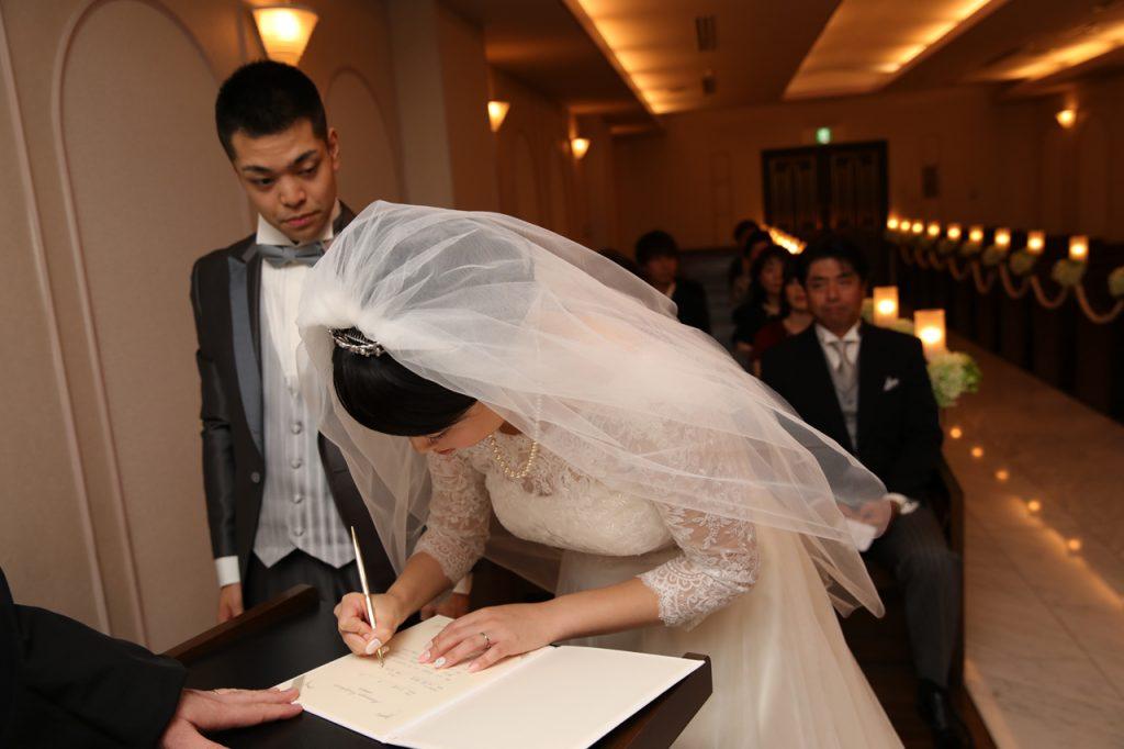 結婚証明書にサインをする新婦