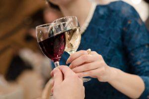 ワインの入ったグラスで乾杯をする女性