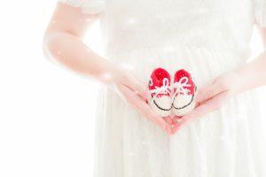 赤ちゃんの靴を持った妊婦